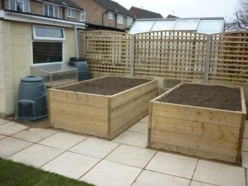 Close space square trellis with a curved top with raised bed planters in front.