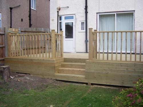 Raised wooden decking with balustrade and steps down to the garden.