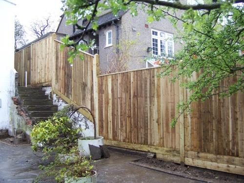 Closeboard fence with capping running up a wall beside a steep set of steps.