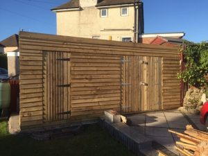 A workshop made with wooden materials and doors supplied by Crestala Fencing.